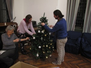 Assistant Librarian Beatrice Gelosia recruits some willing volunteers to decorate the Christmas tree
